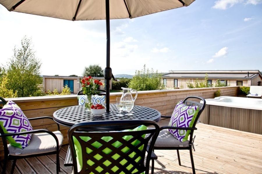 Spacious decking on Perry Lodge with outside seating, hot tub and countryside views